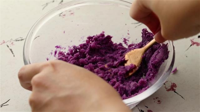 Steam and mash purple sweet potato with a fork
