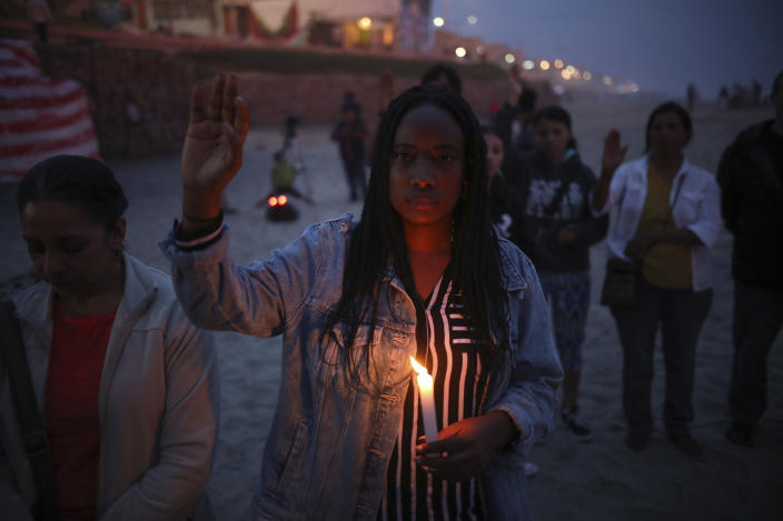 A woman holding a candle observes one minute of silence in memory of migrants who have died during their journey toward the U.S., a few steps from the border fence that separates Mexico from the United States, in Tijuana, Mexico, late Saturday, June 29, 2019. (AP Photo/Emilio Espejel)