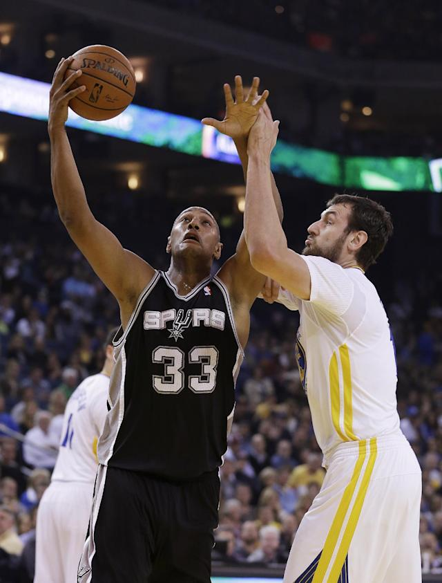 San Antonio Spurs forward Boris Diaw, left, goes to the basket against Golden State Warriors center Andrew Bogut, right, during the first quarter of their NBA basketball game Saturday, March 22, 2014, in Oakland, Calif. (AP Photo/Eric Risberg)