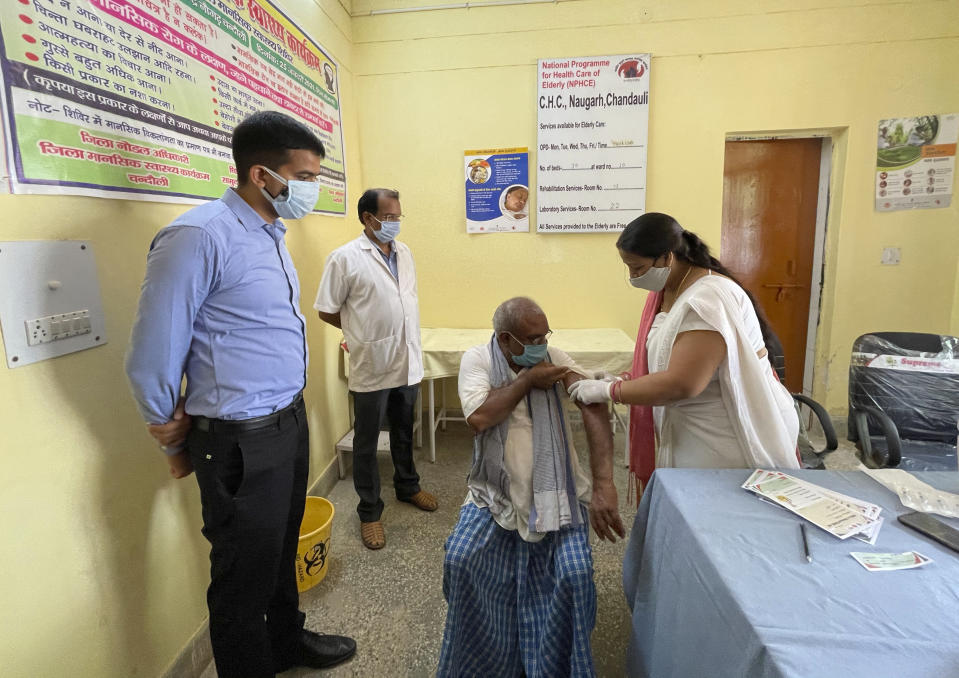 District magistrate Sanjeev Singh, left, overlooks a health worker administering vaccine to a villager at Naugarh, Uttar Pradesh state, India, on June 10, 2021. India's vaccination efforts are being undermined by widespread hesitancy and fear of the jabs, fueled by misinformation and mistrust. That's especially true in rural India, where two-thirds of the country's nearly 1.4 billion people live. (AP Photo/Rajesh Kumar Singh)