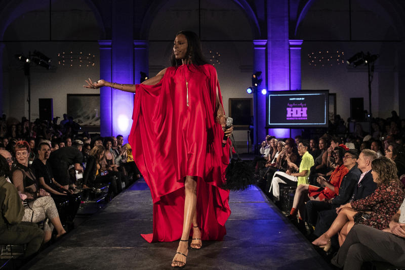 Red carpet host B. Hawk Snipes stands on the stage during dapperQ fashion show at the Brooklyn Museum on Thursday, Sept. 5, 2019, in New York. (AP Photo/Jeenah Moon)