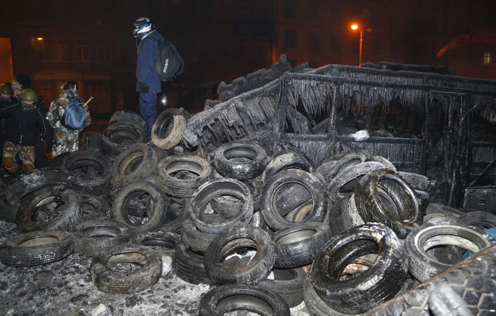 """Protesters stand on the barricade in central Kiev, Ukraine, early Friday Jan. 24, 2014. A top Ukrainian opposition leader on Thursday urged protesters to maintain a shaky cease-fire with police after at least two demonstrators were killed in clashes this week, but some in the crowd appeared defiant, jeering and chanting """"revolution"""" and """"shame."""" (AP Photo/Sergei Grits)"""