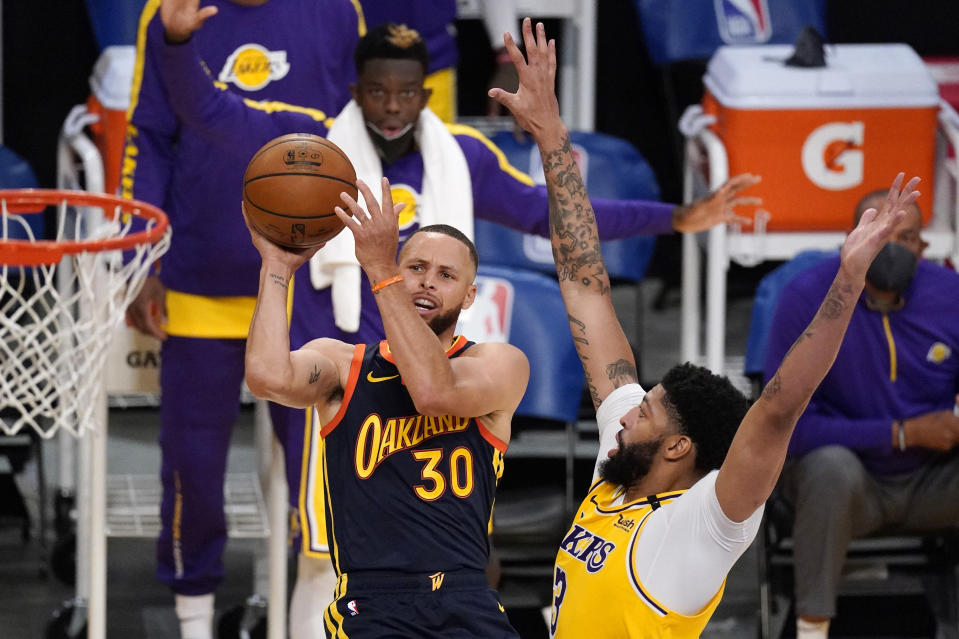 Golden State Warriors guard Stephen Curry, left, shoots as Los Angeles Lakers forward Anthony Davis defends during the second half of an NBA basketball Western Conference Play-In game Wednesday, May 19, 2021, in Los Angeles. (AP Photo/Mark J. Terrill)
