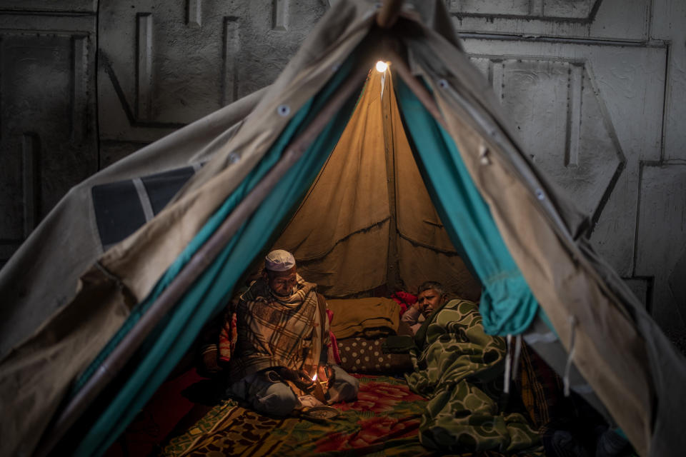 A farmer lights a bidi, or hand-rolled tobacco, as he sits inside a tent with a fellow farmer, blocking a major highway in protest against new farm laws at the Delhi-Uttar Pradesh state border, India, Friday, Jan. 8, 2021. (AP Photo/Altaf Qadri)