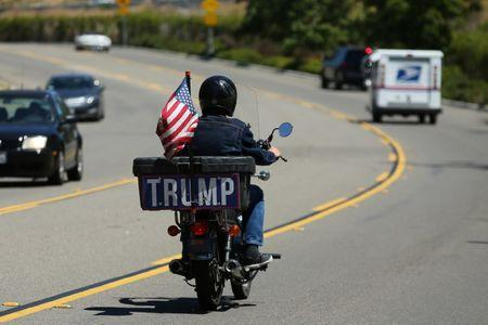 A lone pro-Trump supporter drives off on his motorcycle after shadowing a demonstration against the Republican healthcare bill outside Republican Congressman Darrell Issa's office in Vista, California. REUTER Mike Blake