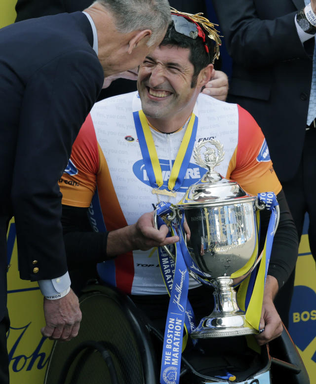 Ernst Van Dyk, of South Africa, is presented the trophy after winning the men's wheelchair division of the 118th Boston Marathon Monday, April 21, 2014 in Boston. (AP Photo/Charles Krupa)