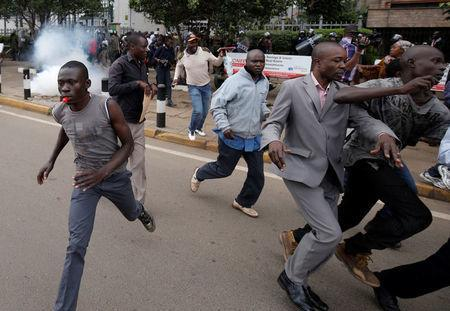 Supporters of Kenya's opposition Coalition for Reforms and Democracy (CORD) run away after riot police lobbed teargas canisters to disperse them during a protest at the premises hosting the headquarters of Independent Electoral and Boundaries Commission (IEBC) to demand the disbandment of the electoral body ahead of next year's election in Nairobi, Kenya, May 23, 2016. REUTERS/Goran Tomasevic