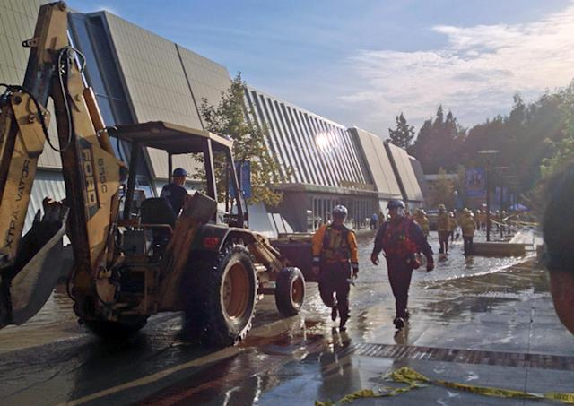 Workers approach Pauley Pavilion, home of UCLA basketball, left, after a 30-inch water main burst on nearby Sunset Boulevard Tuesday, July 29, 2014, in Los Angeles. Water also reached the playing floor of the basketball arena. (AP Photo/Matt Hamilton)