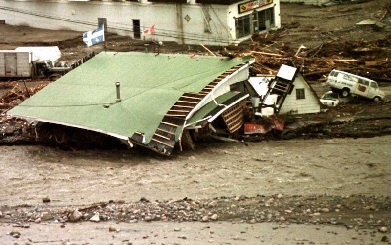 <p>On July 23, 1996, a bank in Chicoutimi, Que., can be seen in ruins due to flooding as the flags of Quebec and Canada continue to fly. Photo from Getty Images. </p>