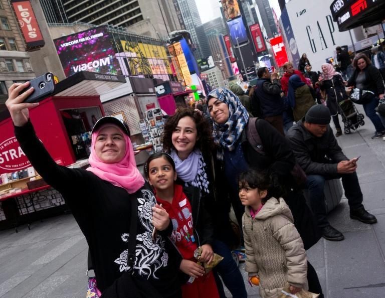 Syrian and Iraqi refugee families take selfies in Times Square during a tour of Manhattan in New York