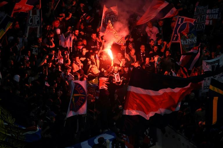 Paris Saint-Germain's supporters hold flags and burn a flare on April 1, 2017, at the Parc Olympique Lyonnais stadium in Decines-Charpieu, near Lyon