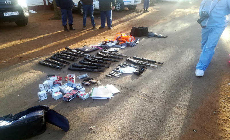 In this photo made available by the South African Police Services (SAPS), confiscated arms and ammunition, lay on the ground at a church in Zuurbekom, near Johannesburg, Saturday, July 11, 2020. Police in South Africa say five people are dead and more than 40 have been arrested after an early-morning hostage situation at a church near Johannesburg. (South African Police Services via AP)