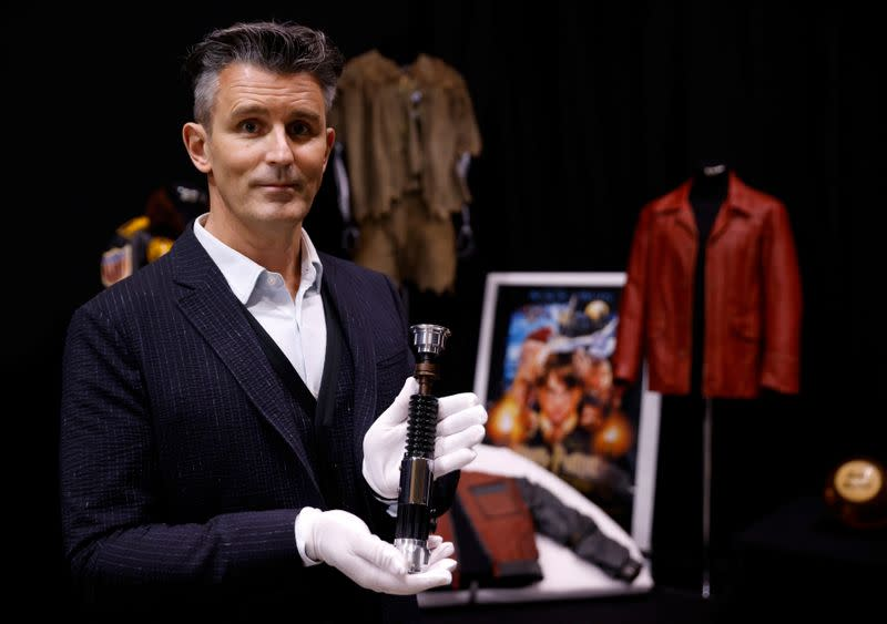 Stephen Lane, CEO of Prop Store, poses for a photograph with Obi-Wan Kenobi's Hero Lightsaber from Star Wars: Revenge of the Sith, at a preview of a movie and TV memorabilia auction in Rickmansworth
