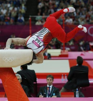 MEDAL RESHUFFLE AFTER FALL: A judge watches as Kohei Uchimura of Japan falls off the pommel horse during the men's gymnastics team final in the North Greenwich Arena during the London 2012 Olympic Games July 30, 2012.