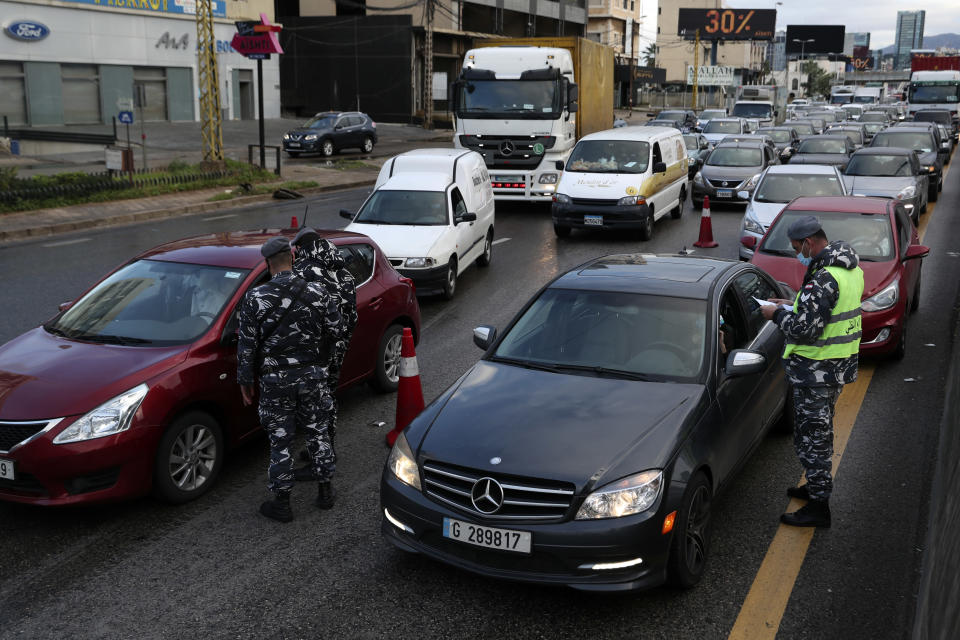 Police officers stand at a checkpoint to inspect cars that violate the lockdown, in Beirut, Lebanon, Thursday, Jan. 14, 2021. Lebanese authorities began enforcing an 11-day nationwide shutdown and round the clock curfew Thursday, hoping to limit the spread of coronavirus infections spinning out of control after the holiday period. (AP Photo/Bilal Hussein)