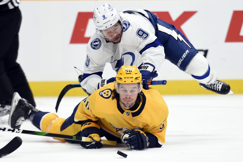 Tampa Bay Lightning center Tyler Johnson (9) falls onto Nashville Predators left wing Erik Haula (56) as they chased the puck during the first period of an NHL hockey game Tuesday, April 13, 2021, in Nashville, Tenn. (AP Photo/Mark Zaleski)