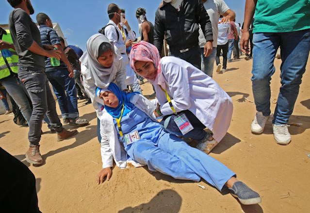 <p>Palestinian woman medics tend to an injured colleague during clashes near the border with Israel, east of Khan Yunis in the southern Gaza Strip on May 15, 2018, amidst protests marking 70th anniversary of Nakba — also known as Day of the Catastrophe in 1948 — and against the US' relocation of its embassy from Tel Aviv to Jerusalem. (Photo: Said Khatib/AFP/Getty Images) </p>