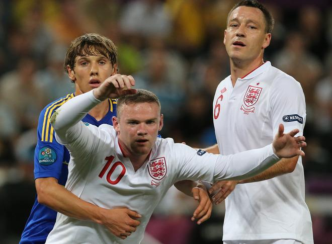 Ukrainian midfielder Denys Garmash (L) vies with English forward Wayne Rooney and English defender John Terry (R) during the Euro 2012 football championships match England vs Ukraine on June 19, 2012 at the Donbass Arena in Donetsk.  AFP PHOTO / ALEXANDER KHUDOTEPLYAlexander KHUDOTEPLY/AFP/GettyImages