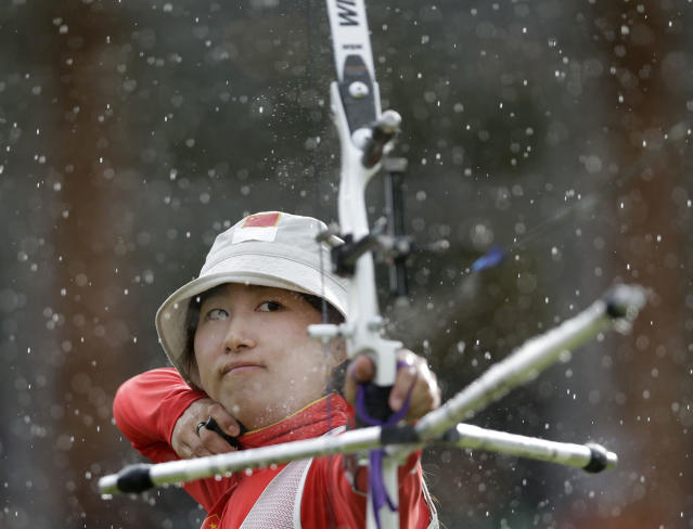 China's Fang Yuting shoots in the rain for a silver medal during the women's archery team competition at the 2012 Summer Olympics, Sunday, July 29, 2012, in London. (AP Photo/Marcio Jose Sanchez)