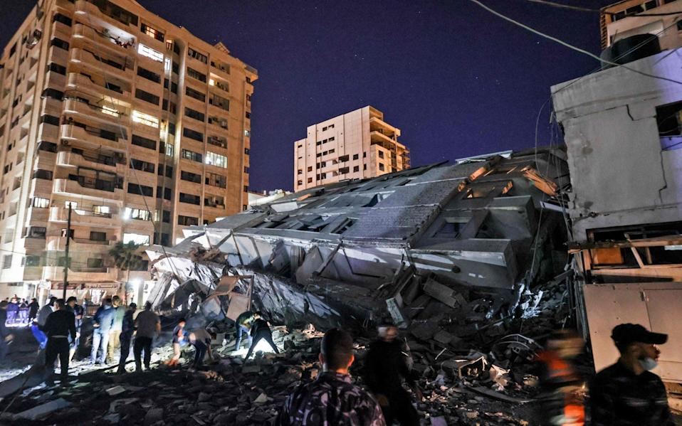 People gather at the site of a collapsed building in the aftermath of Israeli air strikes on Gaza City - AFP