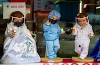 Some dolls wear baby clothes and face masks, while others sport medical gowns or white laboratory coats