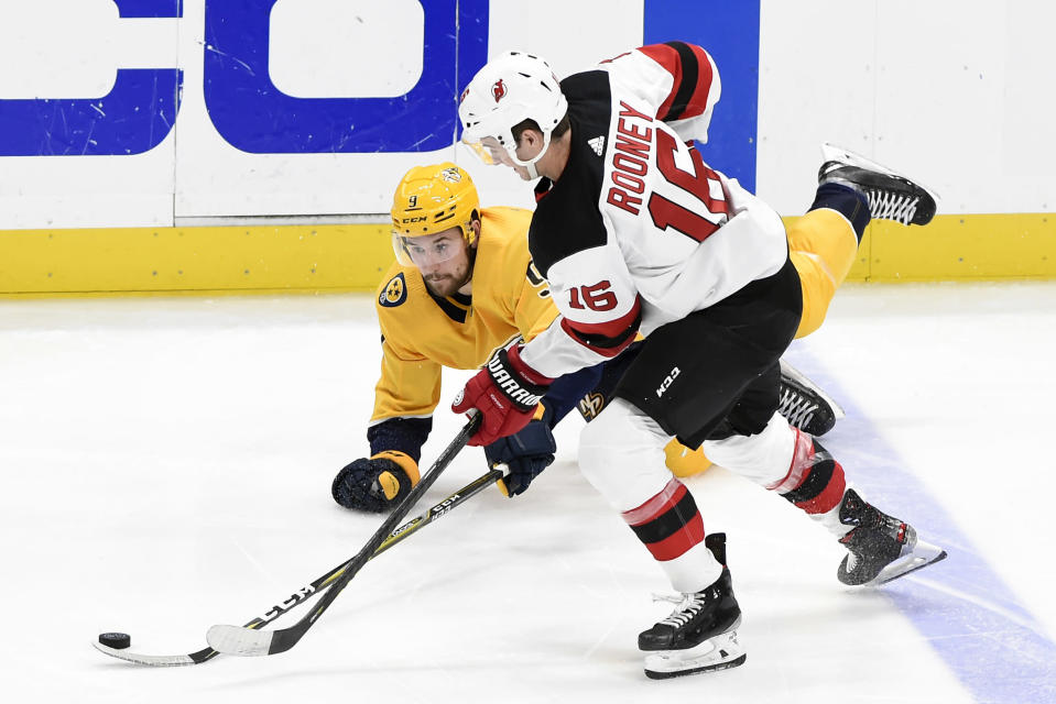 Nashville Predators left wing Filip Forsberg (9), of Sweden, clears the puck away from New Jersey Devils center Kevin Rooney (16) during the third period of an NHL hockey game Saturday, Dec. 7, 2019, in Nashville, Tenn. The Predators won 6-4. (AP Photo/Mark Zaleski)