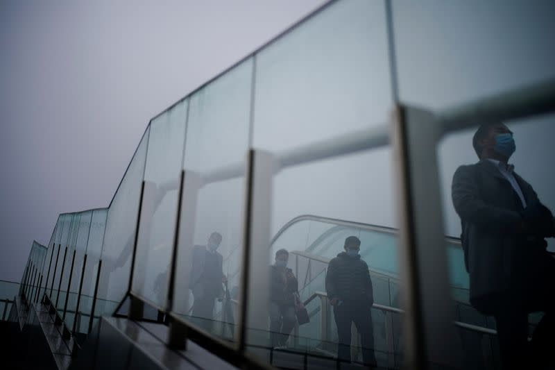 People wearing face masks descend a stairwell following the coronavirus disease (COVID-19) outbreak, in Shanghai