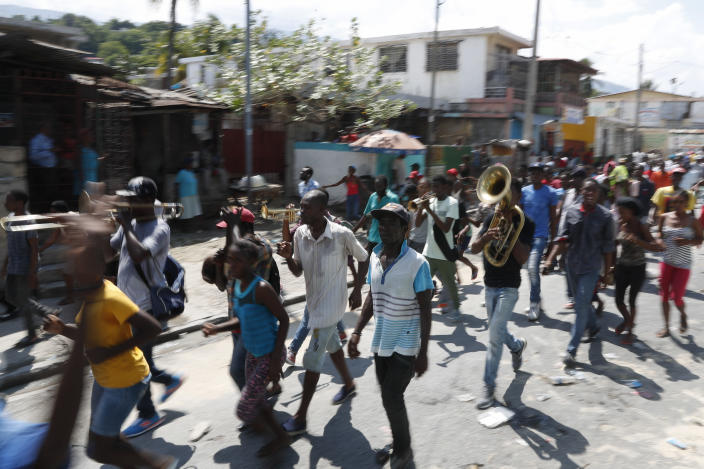 A group of protesters calling for the resignation of President Jovenel Moise march to join others at a bridge in the Delmar area of Port-au-Prince, Haiti, Thursday, Oct. 17, 2019. Haiti's embattled president was forced on Thursday to hold a private ceremony amid heavy security for what is usually a public celebration of one of the country's founding fathers, revolution leader Jean-Jacques Dessalines. (AP Photo/Rebecca Blackwell)