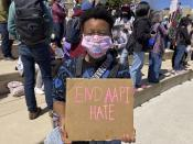 """CORRECTS REFERENCE IN THIRD SENTENCE TO THEY STED OF SHE Camden Hunt poses for a picture at a rally on Saturday, March 20, 2021, across from the Georgia state Capitol in Atlanta to demand justice for the victims of shootings at massage businesses days earlier. A 21-year-old white man is accused of killing eight people, six of them women of Asian descent, at three Atlanta-area massage businesses Tuesday. Hunt said they came out to the rally Saturday to """"show Black and Asian solidarity."""" (AP Photo/Kate Brumback)"""