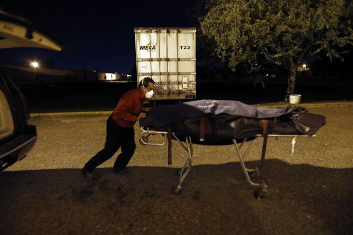 """Juan Lopez went from moving 15 bodies a week before the pandemic to 22 some days. He often works overnight, picking up bodies from hospitals, nursing homes and houses and delivering them to funeral homes or morgues. <span class=""""copyright"""">(Carolyn Cole / Los Angeles Times)</span>"""
