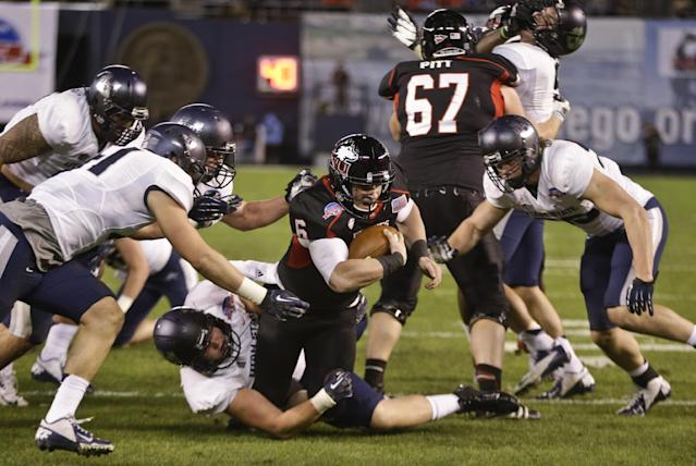 Northern Illinois quarterback Jordan Lynch plows his way through the Utah State defenders while stretching to get a first down at the 1-yard line during the first half of the Poinsettia Bowl NCAA college football game Thursday, Dec. 26, 2013, in San Diego. (AP Photo/Lenny Ignelzi)