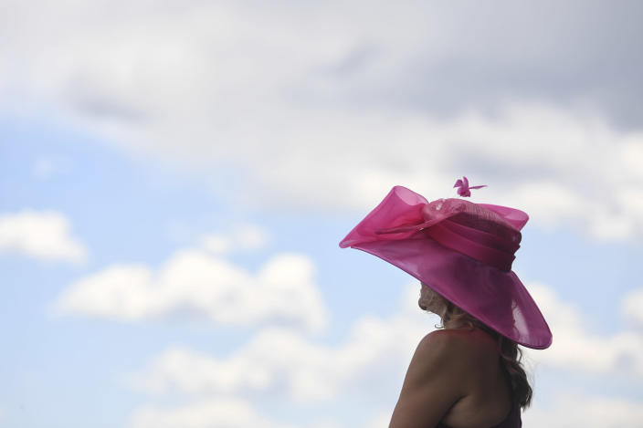 A woman wears a big hat ahead of the Preakness Stakes horse race at Pimlico Race Course, Saturday, May 15, 2021, in Baltimore. (AP Photo/Will Newton)