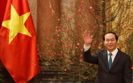 Vietnam's President Tran Dai Quang waves his hand to the media as he waits for arrival of Japan's Prime Minister Shinzo Abe at the Presidential Palace in Hanoi
