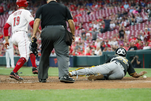 Cincinnati Reds' Joey Votto (19) runs home to score on a throwing error by Pittsburgh Pirates first baseman Josh Bell to catcher Elias Diaz, right, in the second inning of a baseball game, Monday, July 29, 2019, in Cincinnati. (AP Photo/John Minchillo)