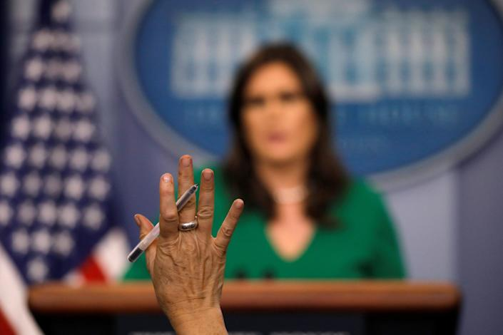 A reporter raises her hand as White House press secretary Sarah Sanders holds the daily briefing at the White House. (Photo: Carlos Barria/Reuters)