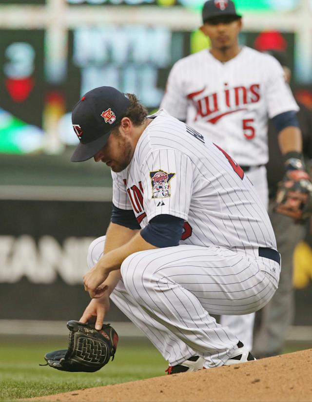 Minnesota Twins pitcher Phil Hughes crouches down after being hit in the ankle with a line drive single off the bat of Chicago White Sox' Adam Dunn in the fourth inning of a baseball game, Thursday, July 24, 2014, in Minneapolis. Hughes left the game moments later. (AP Photo/Jim Mone)