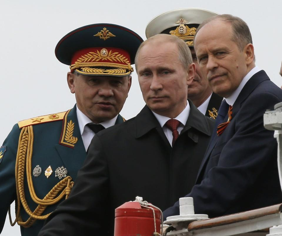 Russian President Vladimir Putin (C), Defence Minister Sergei Shoigu (L) and Russia's Federal Security Service (FSB) Director Alexander Bortnikov watch events to mark Victory Day in Sevastopol May 9, 2014. Putin went to Crimea on Friday for the first time since Russia annexed the peninsula from Ukraine in March, a visit that is likely to anger the Ukrainian leadership and upset the West. REUTERS/Maxim Shemetov (UKRAINE - Tags: POLITICS ANNIVERSARY CONFLICT PROFILE MILITARY)