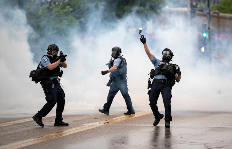 <strong>A police officer throws a tear gas canister towards protesters at the Minneapolis 3rd Police Precinct, following a rally for George Floyd on Tuesday, May 26.</strong> (Photo: ASSOCIATED PRESS)