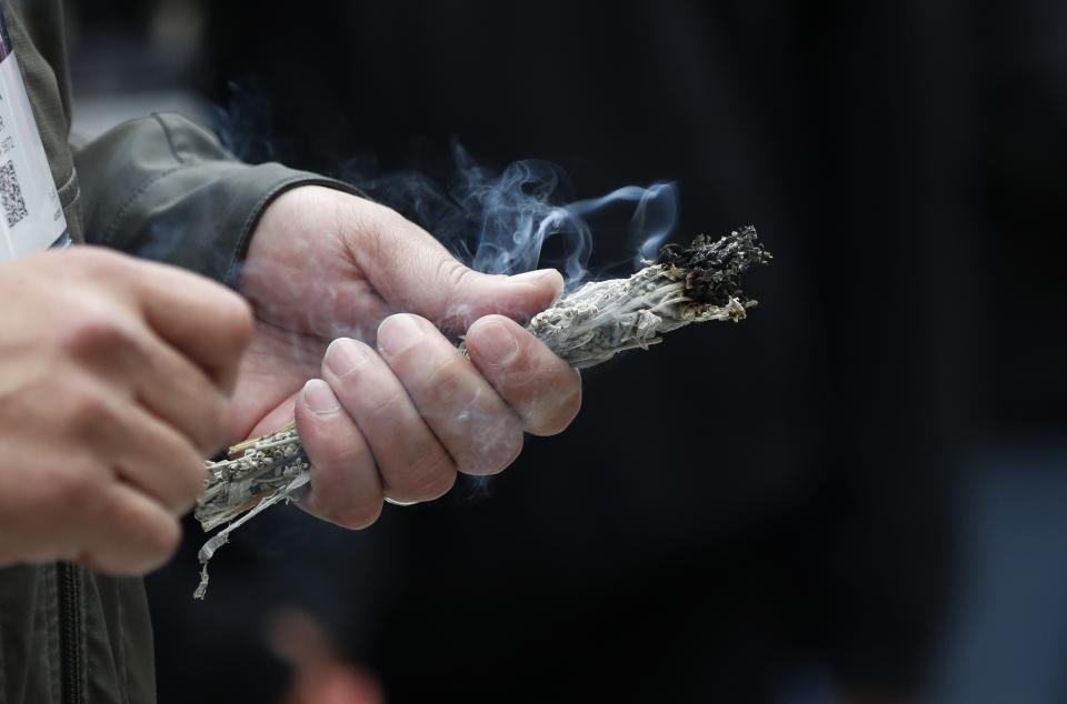 First Nation Chief Duke Peltier holds smoking sage branches during a smudging ceremony, Friday, April 26, 2019, in Detroit. Smudging can help combat negativity, clear the energy in your field, and help you start anew. It is an ancient ceremony in which you burn sacred plants, such as sage, to allow the smoke to clear and bless a space. (AP Photo/Carlos Osorio)