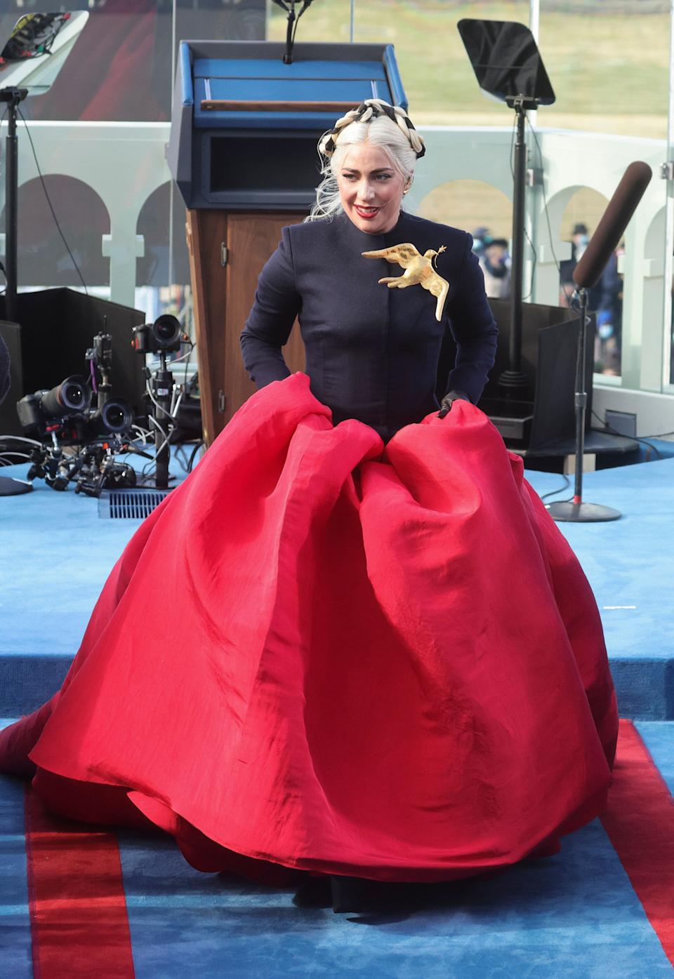 Lady Gaga picks up her skirt after singing the national anthem during the inauguration. (Photo: Pool via Getty Images)