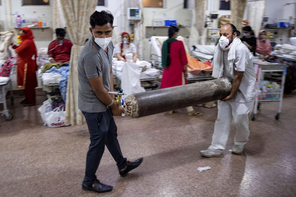 <p>Relatives of a Covid-19 patient carry an oxygen cylinder in the emergency room of a hospital in Delhi on 1 May, 2021. </p> (REUTERS)