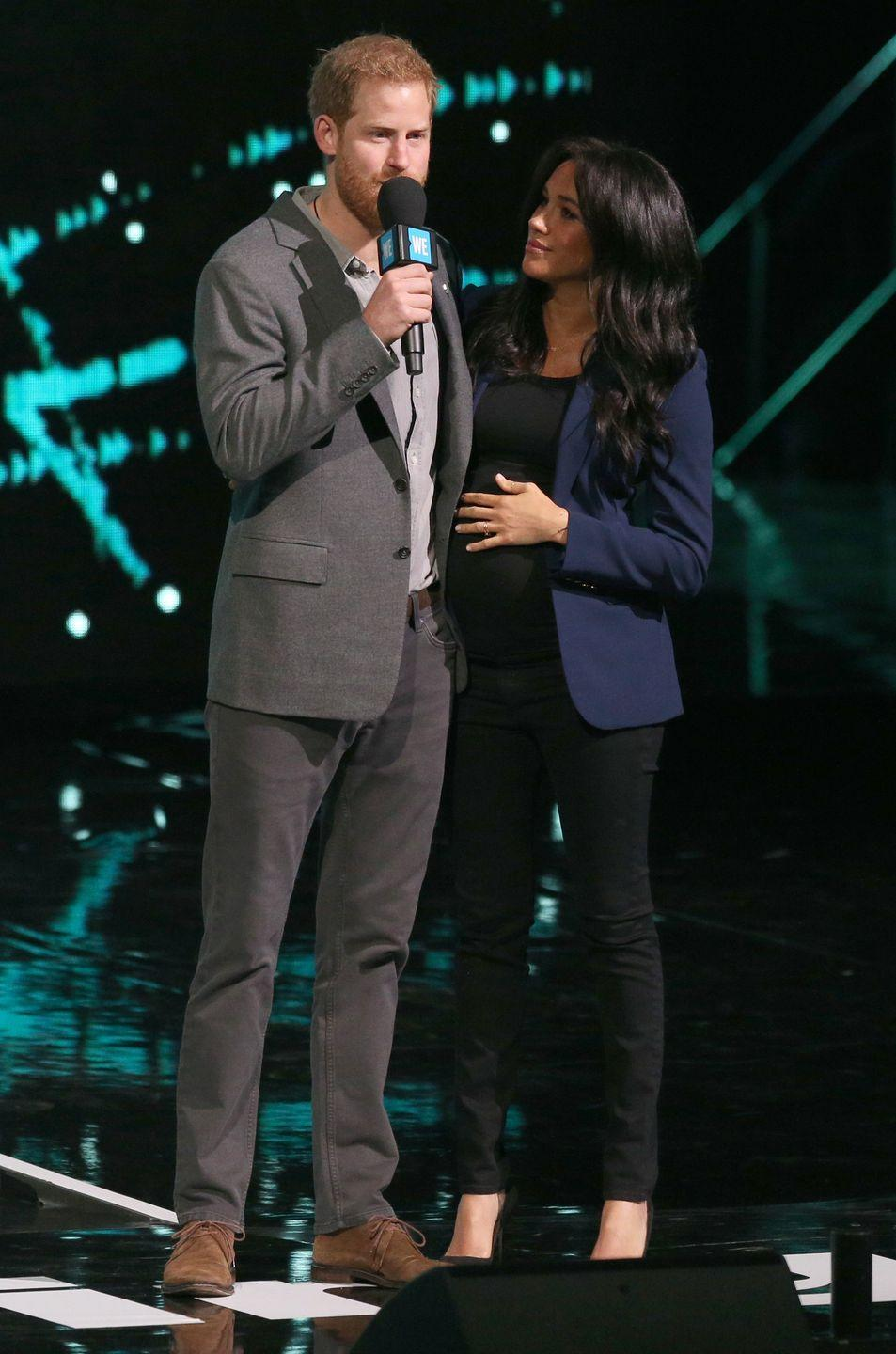 """<p>Meghan surprised crowds by appearing on stage with <a href=""""https://www.townandcountrymag.com/society/tradition/a26708102/prince-harry-we-day-speech-transcript-2019/"""" rel=""""nofollow noopener"""" target=""""_blank"""" data-ylk=""""slk:Prince Harry during his WE Day speech"""" class=""""link rapid-noclick-resp"""">Prince Harry during his WE Day speech</a>. For the event, she wore a navy blazer over a black top, paired by black denim and pumps.</p>"""