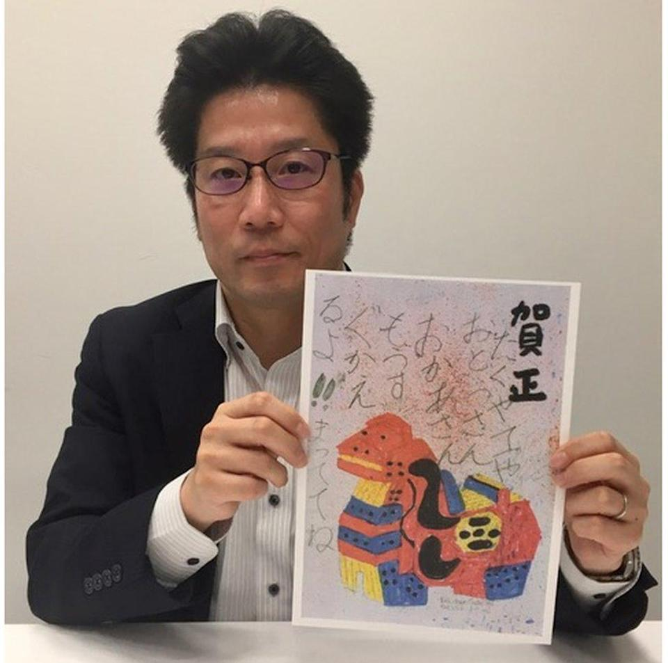 Takuya Yokota, in a black suit, holds up a copy of a postcard featuring a colourful animal