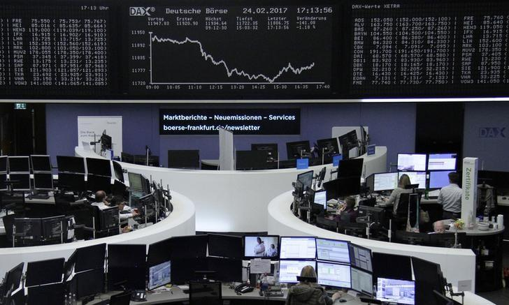 Traders work at their desks in front of the German share price index, DAX board, at the stock exchange in Frankfurt, Germany, February 24, 2017. REUTERS/Staff/Remote