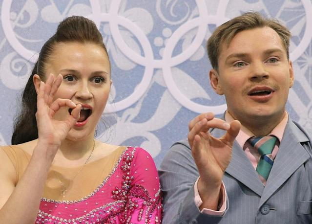 Julia Zlobina and Alexei Sitnikov of Azerbaijan gesture to spectators as they wait in the results area after competing in the ice dance short dance figure skating competition at the Iceberg Skating Palace during the 2014 Winter Olympics, Sunday, Feb. 16, 2014, in Sochi, Russia