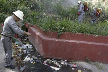 A health worker (L) puts a chemical compound into a puddle to kill mosquito larvae as others fumigate the Valle slum to help control the spread of the mosquito-borne Zika virus in Caracas, January 28, 2016. REUTERS/Marco Bello