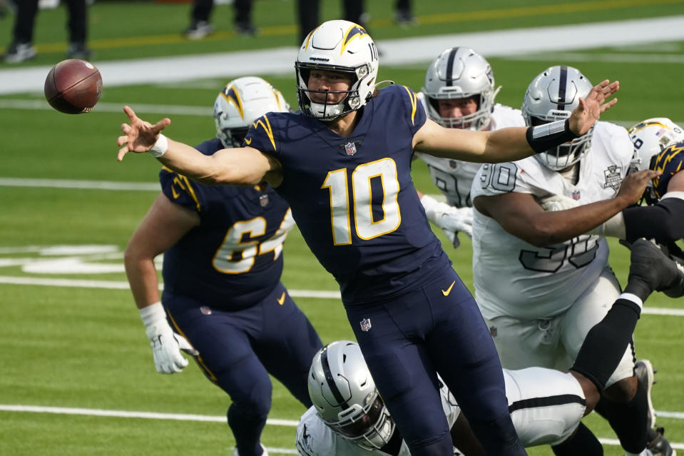 Los Angeles Chargers quarterback Justin Herbert (10) throws a pass under pressure during the first half of an NFL football game against the Las Vegas Raiders, Sunday, Nov. 8, 2020, in Inglewood, Calif. (AP Photo/Ashley Landis)