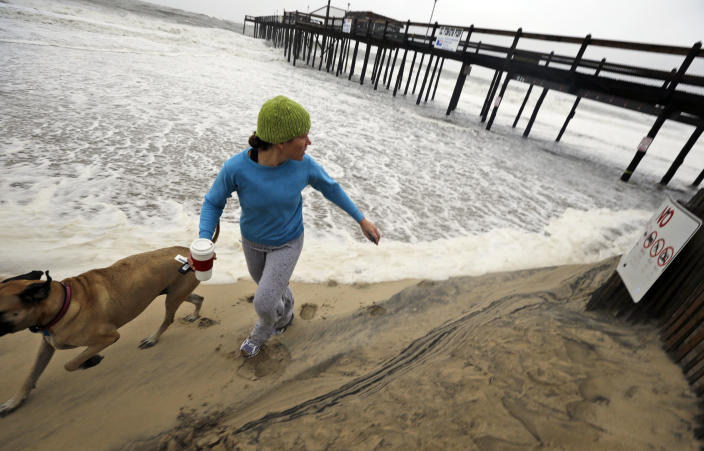 Jenny Lind and her dog Greta run away from a wave that comes up the beach as Hurricane Sandy bears down on the East Coast, Sunday, Oct. 28, 2012, in Ocean City, Md. (AP Photo/Alex Brandon)