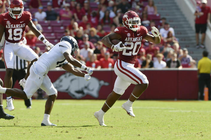 Arkansas running back Dominique Johnson (20) slips past Georgia Southern corner back Darrell Baker Jr. (14) for a big gain during the first half of an NCAA college football game Saturday, Sept. 18, 2021, in Fayetteville, Ark. (AP Photo/Michael Woods)
