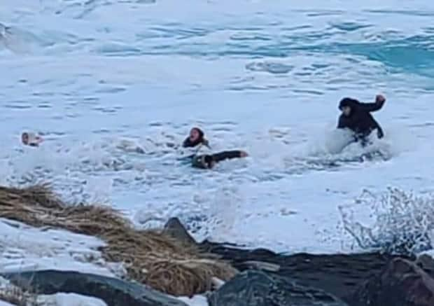 Two children were dragged into the water on Middle Cove Beach Friday following large swells and rising tide in the area. (Donna Paddon/Twitter - image credit)